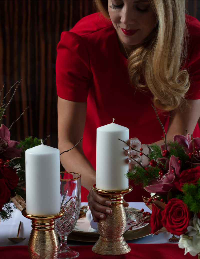 Angie of Angie's Tables setting up the Father Christmas Tablescape, white candles with gold candle holders
