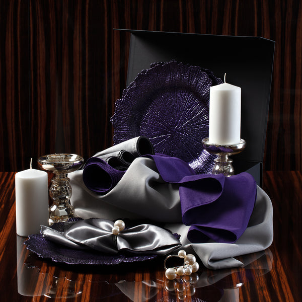 New Years OX Metal Tablescape Kit items including purple chargers and runner, silver tablecloth, silver napkins, pearl napkin rings, large pillar candles on metal glass holders.