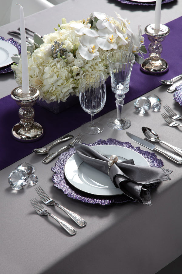 Angie's Tables New Years OX Metal Tablescape single setting with purple chargers and table runner,  silver napkins, pearl napkin rings.