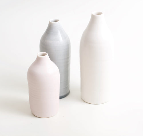 Elegant handmade slim bottles, handmade by London based ceramicist Linda Bloomfield. The slim porcelain bottles are beautifully finished with a tactile satin matt glaze. Truly stunning pottery for display, vase or water bottle, that look as striking on their own as they do grouped together.   Available in Grey (17cm height), Pink (15cm), White (21cm)