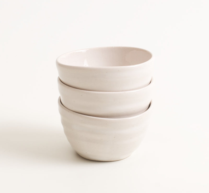 Handmade white porcelain bowls that are the perfect size for dipping sauces or small snacks in the kitchen. The porcelain bowls have a subtle coloured glaze on the inside and a tactile satin matt glaze on the outside, a wonderful aesthetic.   Would also be lovely used elsewhere in the home for storing jewellery, accessories, small pieces of stationery.   Dimensions: 6.5 cm X 6.5cm X 4cm