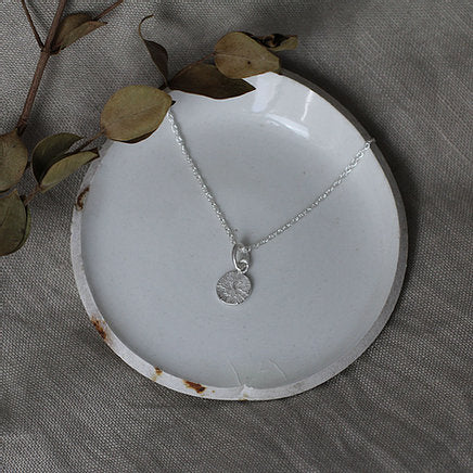 Textured shapes necklace with a round tag made out of recycled silver by April March Jewellery, sold by Percy Langley