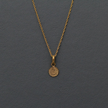 Textured shaped necklace with a round tag made out of fairmined gold vermeil by April March Jewellery, sold by Percy Langley
