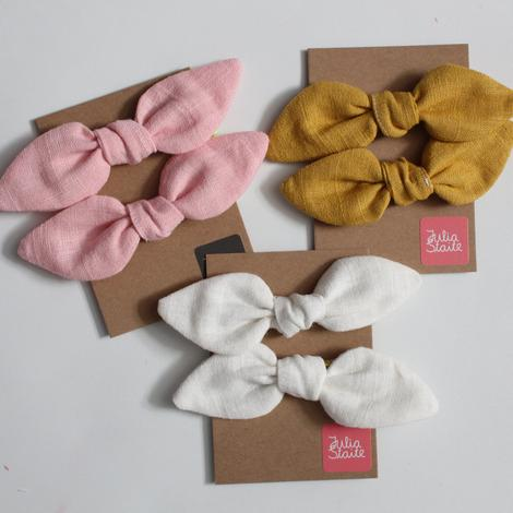 A set of two beautiful linen bow hair elastics by designer Julia Staite.  Made from 100% linen and 3 colours to choose from: White with gold elastic Mustard with neon pink elastic Pink with neon yellow elastic  Each bow approx. 6cm