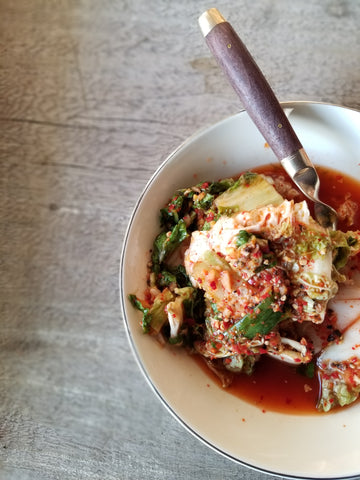 kimchee in bowl with wooden spoon