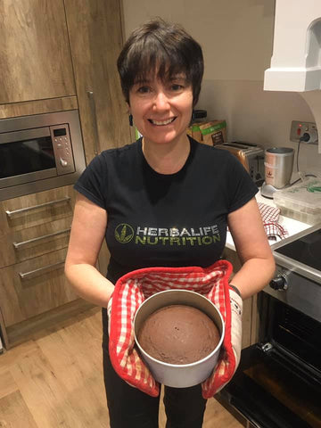 lady holding chocolate cake fresh from the oven
