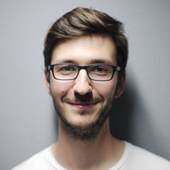 Happy young man with glasses smiling but not showing his teeth
