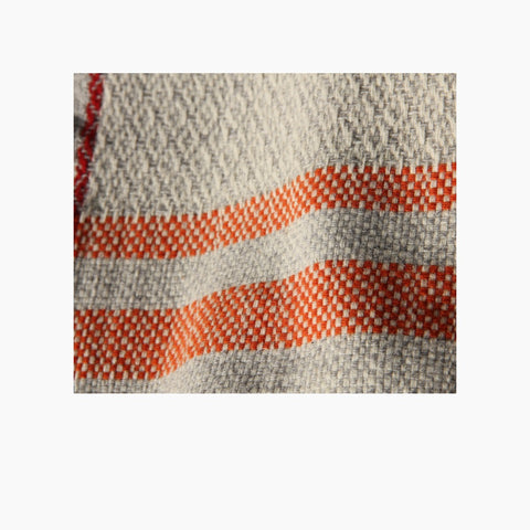 detail which belongs to poncho Serra da Estrela; orange stripes and hand knotted fringes