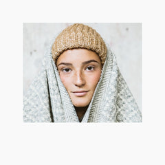 beautiful portrait of a woman who is wearing a recycled wool beanie, combined with the fact that she is wrapped in a blanket