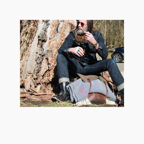 picture of a beautiful guy sitting against a tree with a leather bag between his legs in which our poncho Belmonte is folded