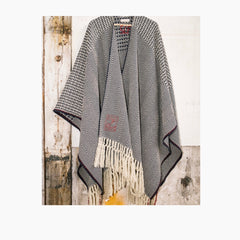 picture of hanging poncho in blue and off white, and with a red selvedge detail along the side seams