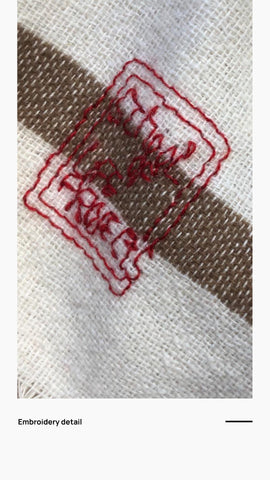Detail of the embroidery on the front of the poncho in red saying 'SchoolofLifeProjects'