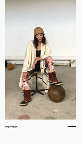Picture of sitting women in colored leggings wearing the off white poncho with the color tipped embroidery