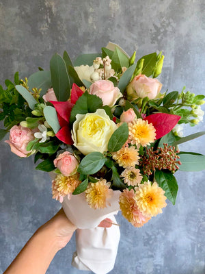 A pink and yellow bouquet created by Roses and Twine Florist in Mill Hill, London containing roses, dahlias, snowberries and eucalyptus.