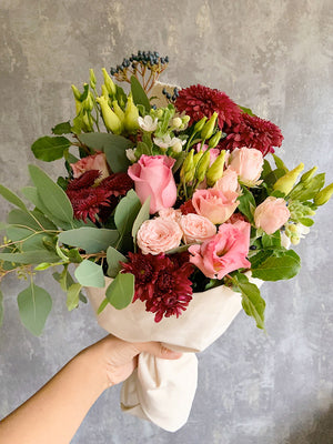 A red and pink seasonal bouquet of flowers created by Roses and Twine Florist in Mill Hill, London. The bunch of flowers contains red dahlias, pink roses and eucalyptus.