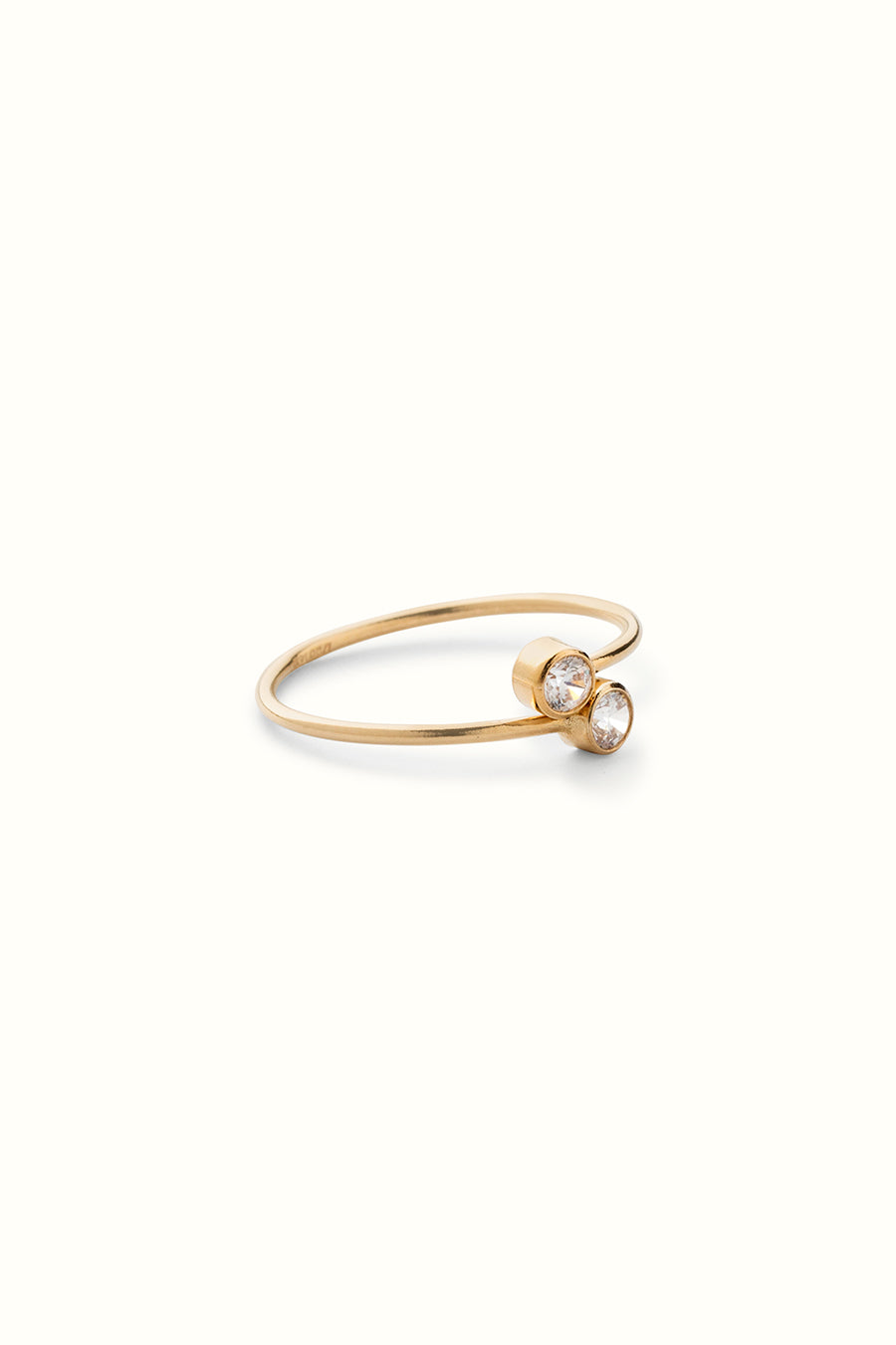 a gold filled fine adjustable finger ring with two zirconia gemstones lying on a white surface