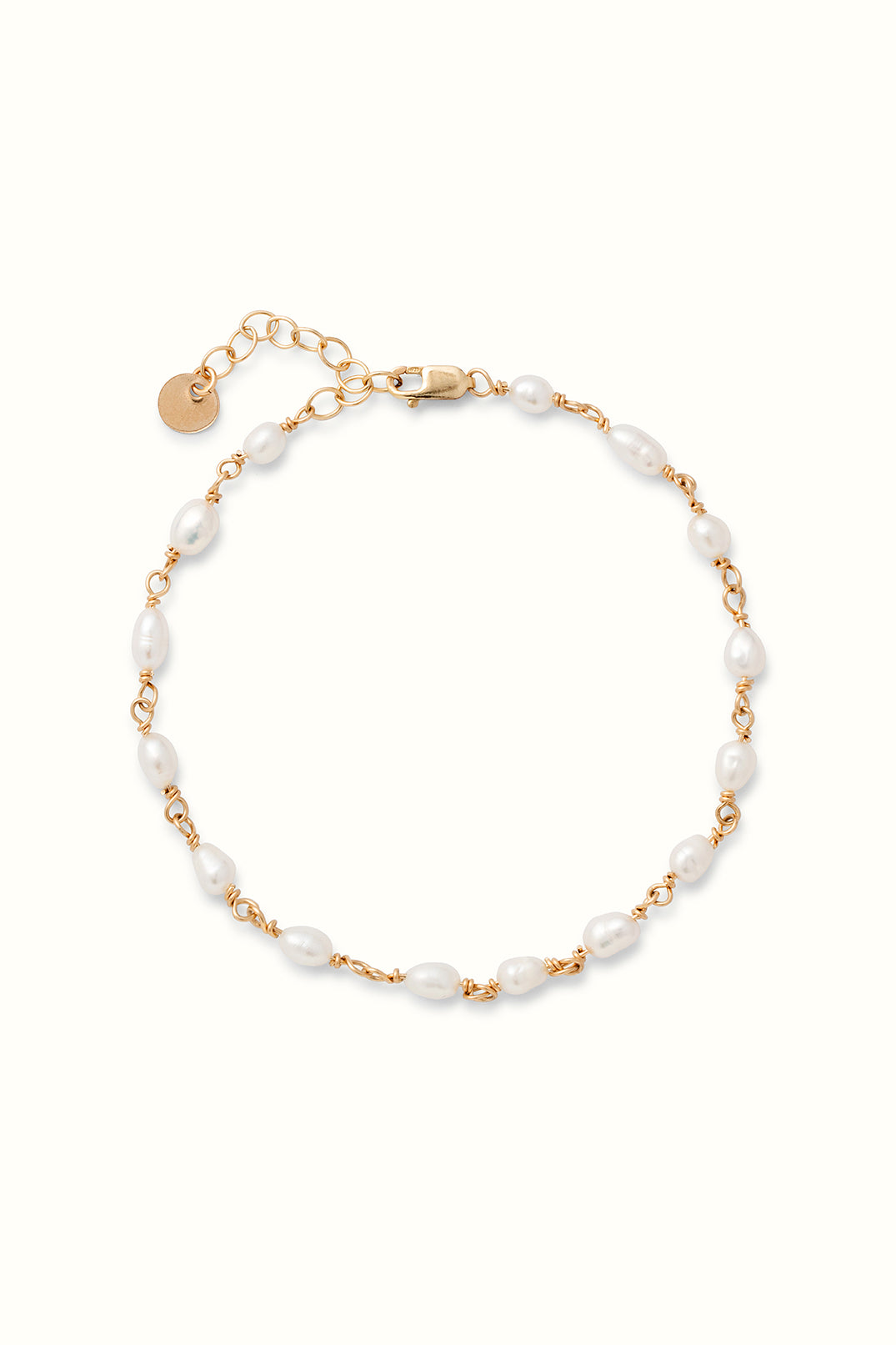 a gold filled pearl rosary bracelet lying on a white surface