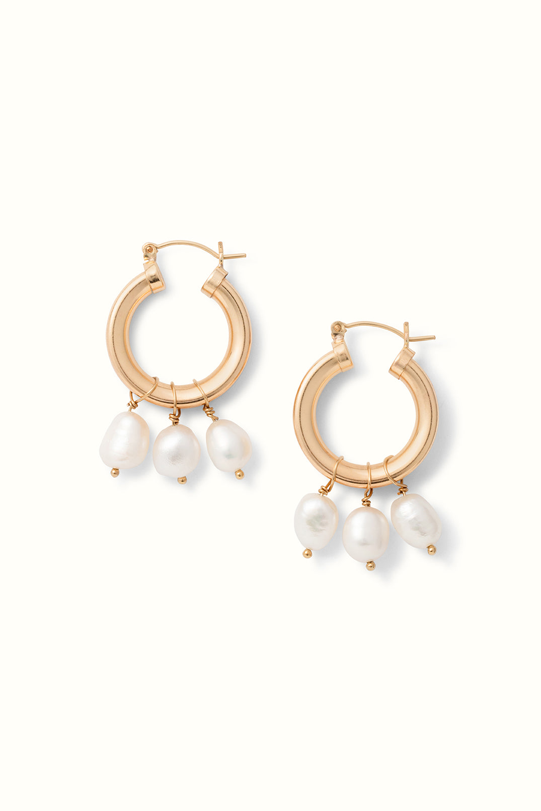 two chunky gold filled hoops with both 3 pearl drops lying on a white surface