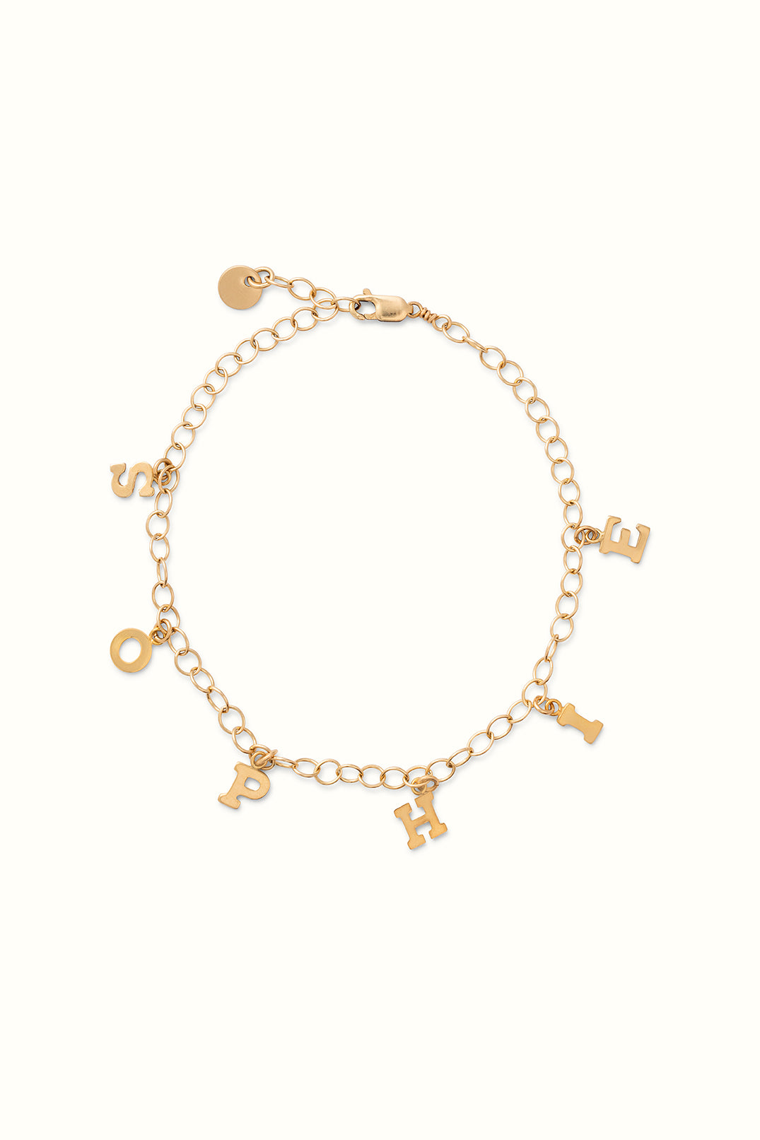 a close up of a gold filled initial charm bracelet