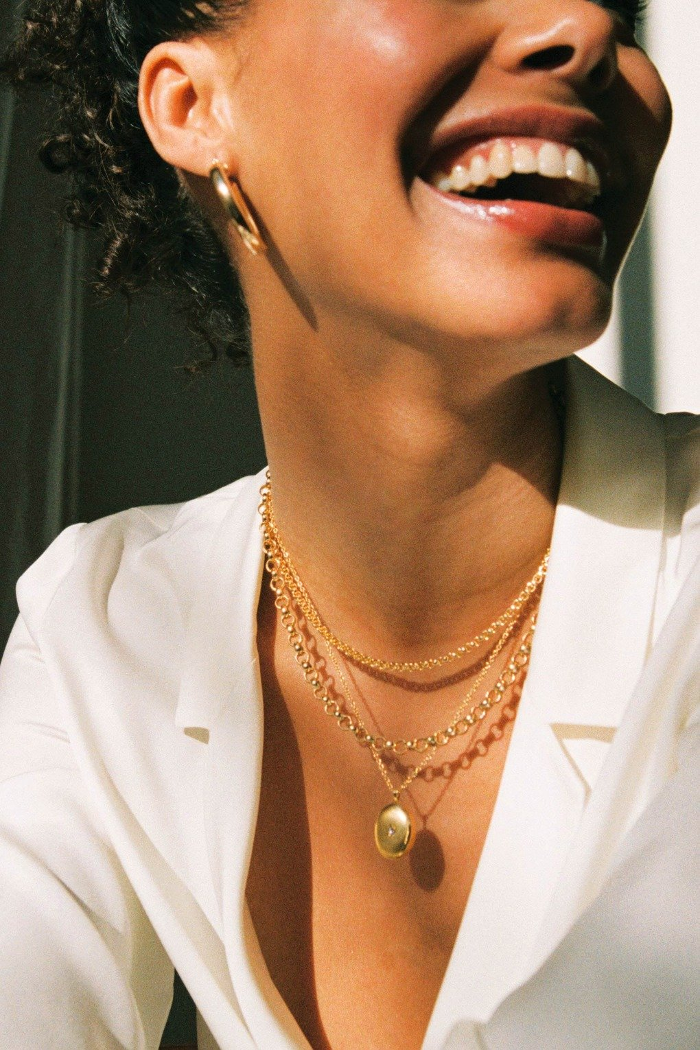 a young woman wearing a matching set of three gold filled necklaces