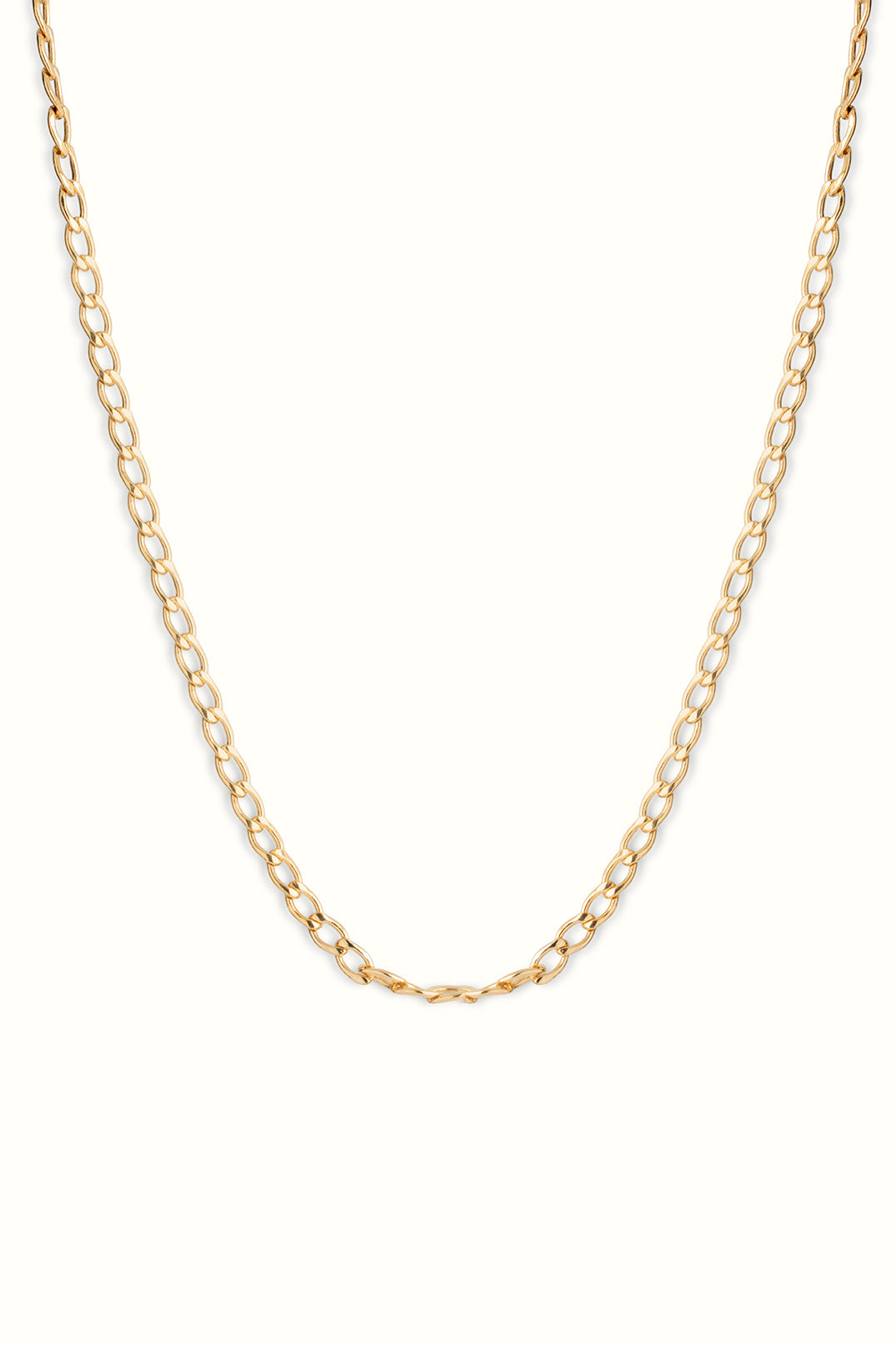 a close up photo of a gold filled chunky curb chain necklace hanging in front of a white background
