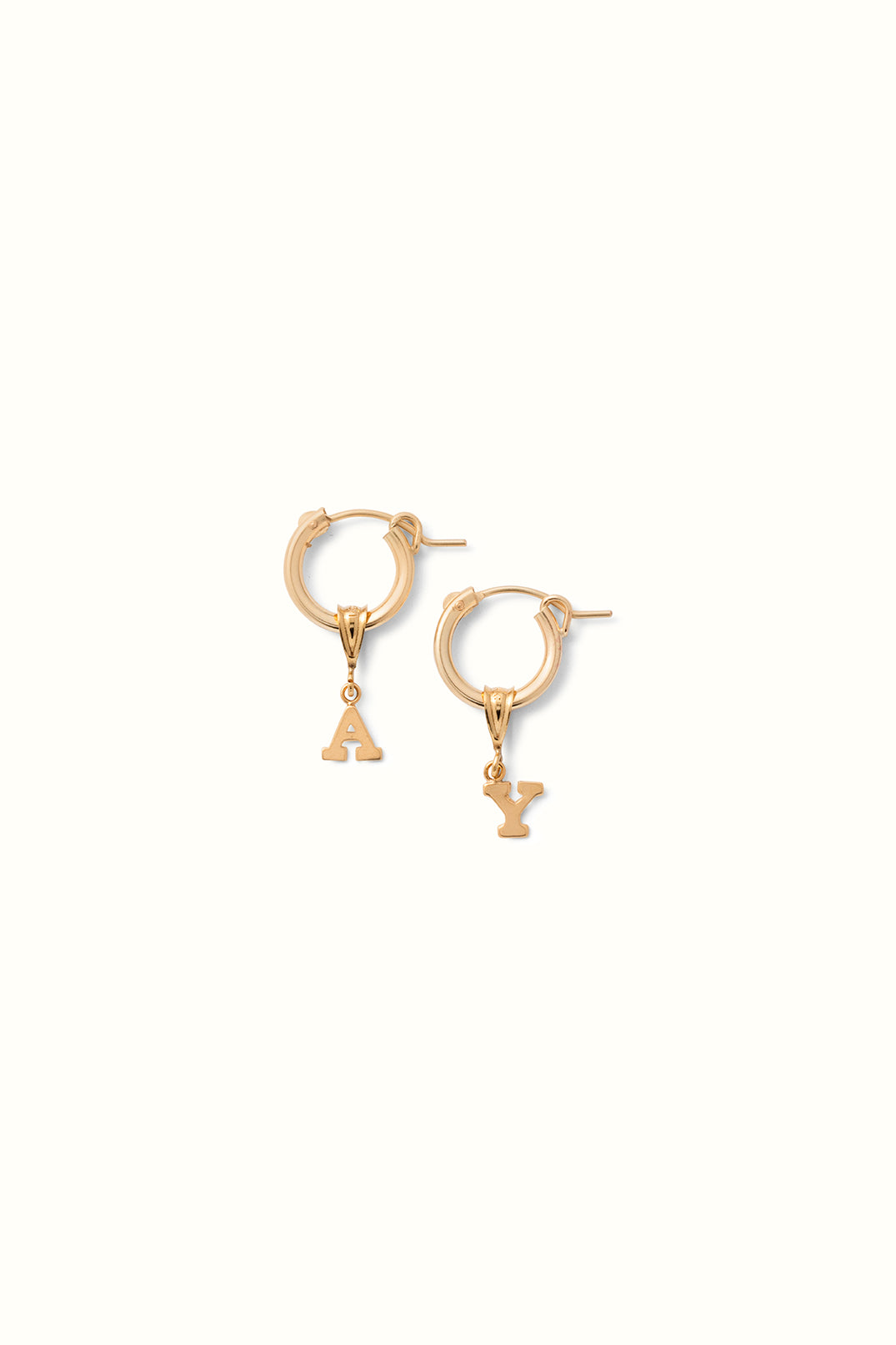 a close up photo of a set of gold filled earring hoops with initial pendant charms