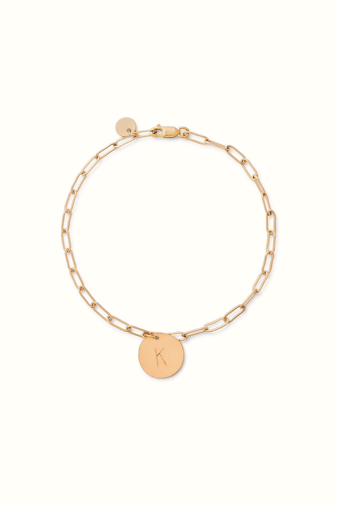 a gold filled paperclip chain bracelet with a round initial pendant lying on a white surface