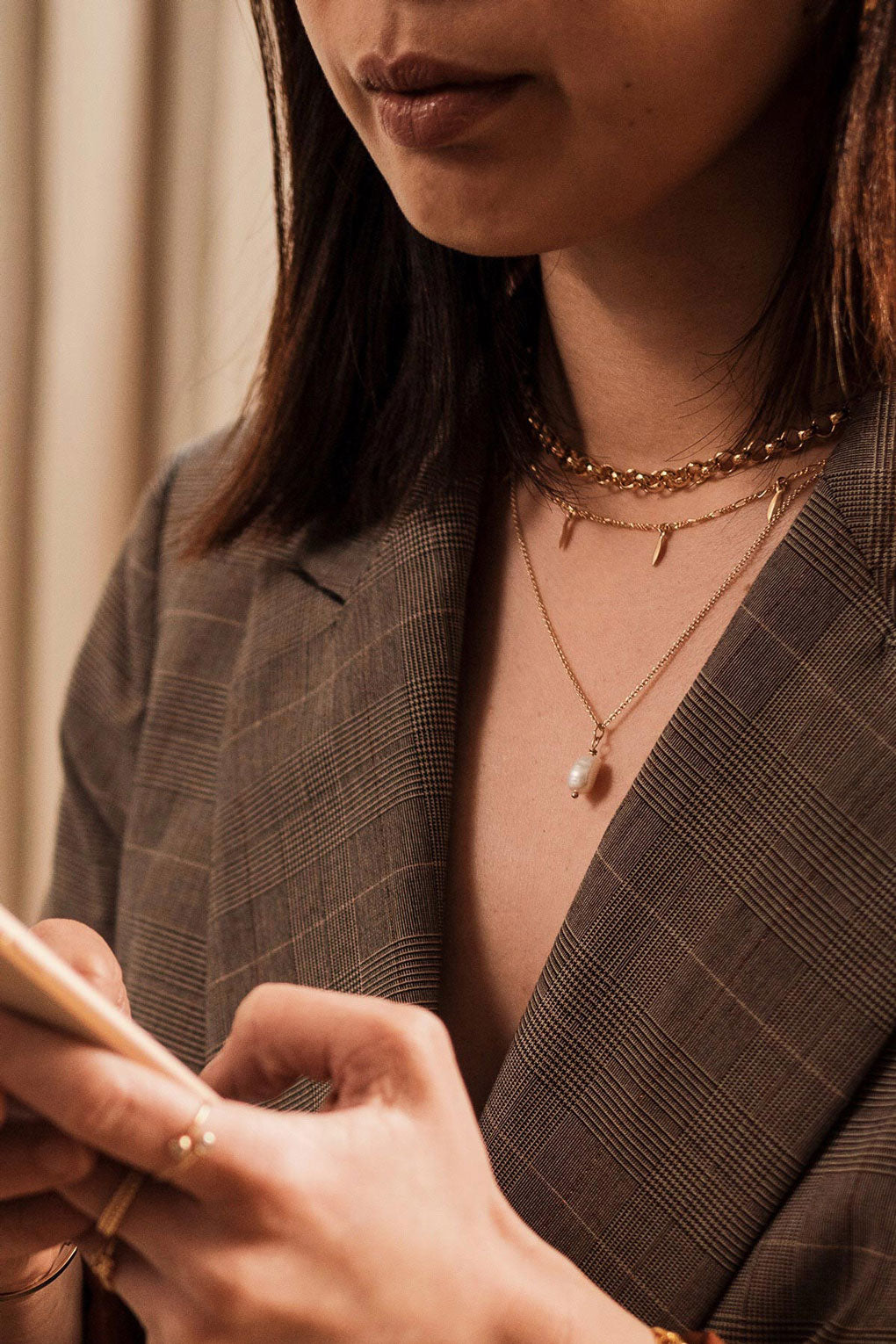 a combination of fine and chunky gold filled necklaces worn by a model