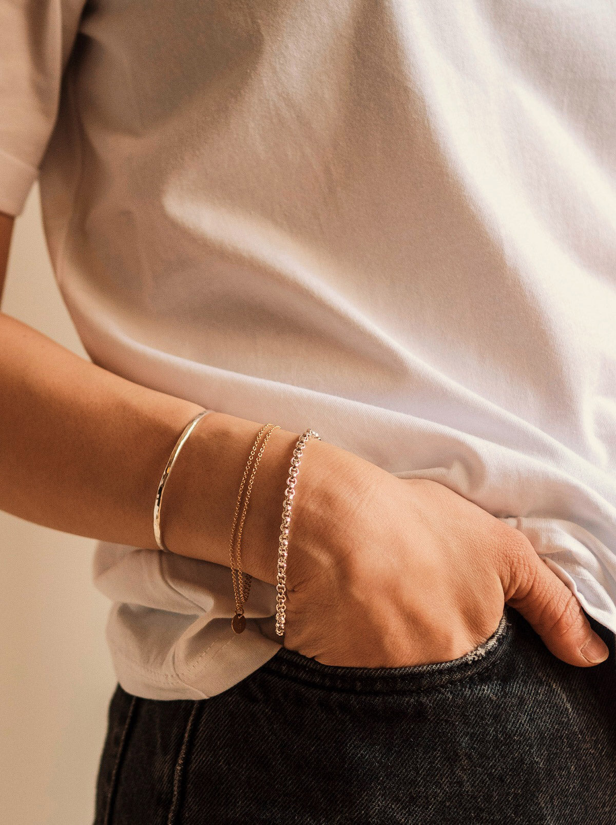 a woman wearing a sterling silver cuff bracelet combined with other gold filled and sterling silver bracelets