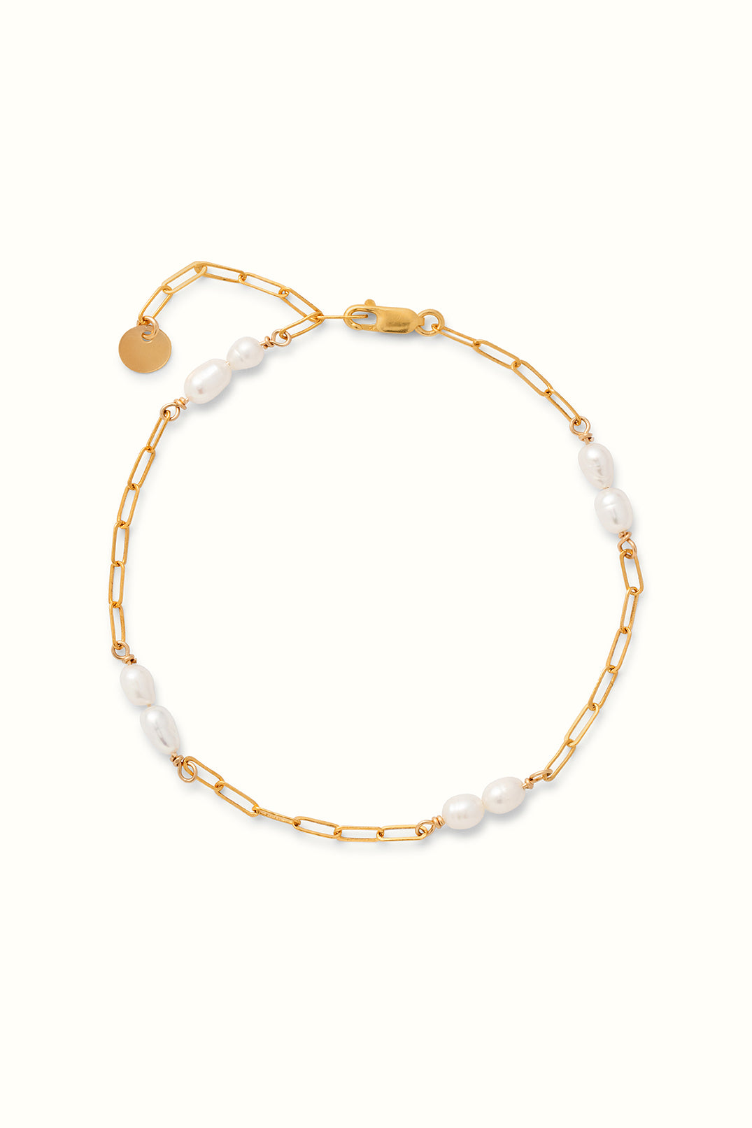 close up of a gold filled paperclip chain and pearl bracelet on a white surface