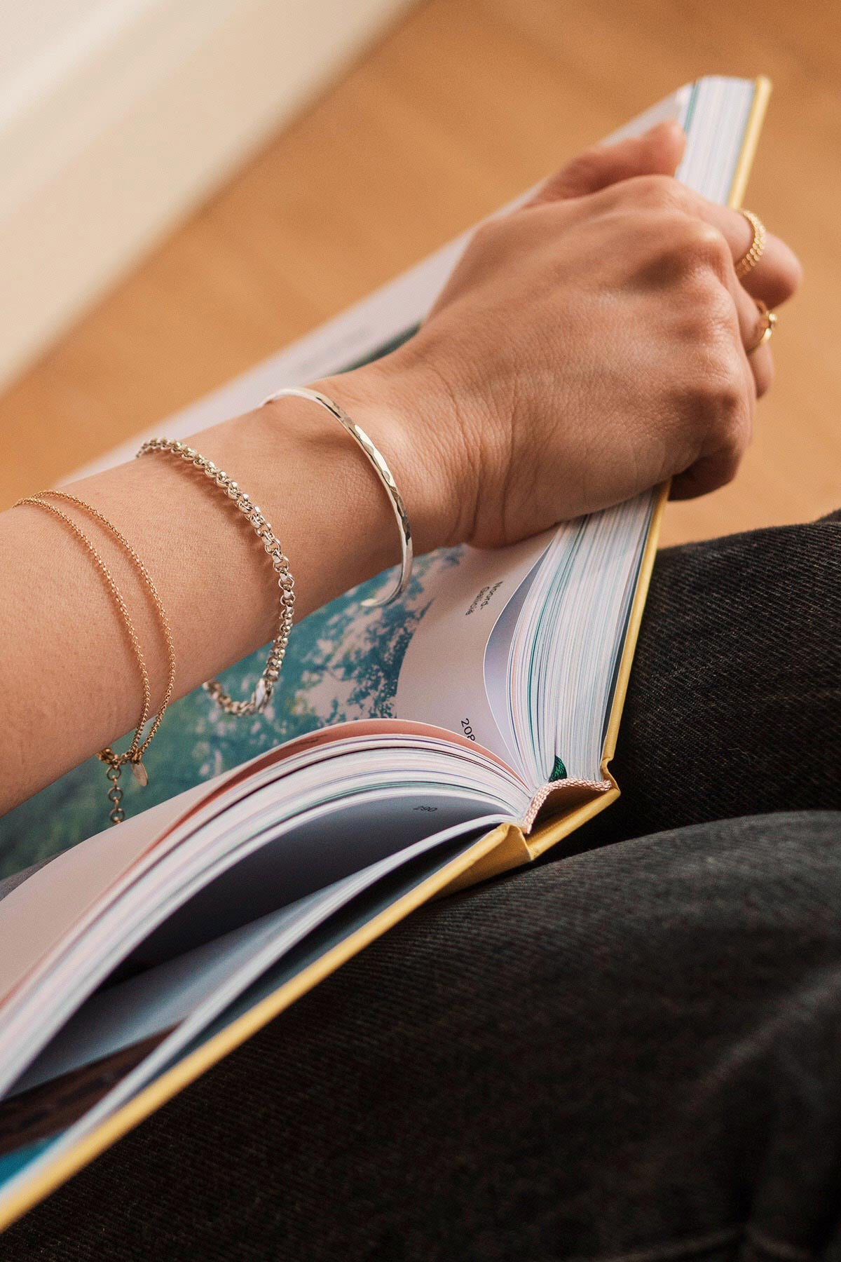 woman wearing a sterling silver hammered cuff bracelet combined with other silver and gold filled bracelets