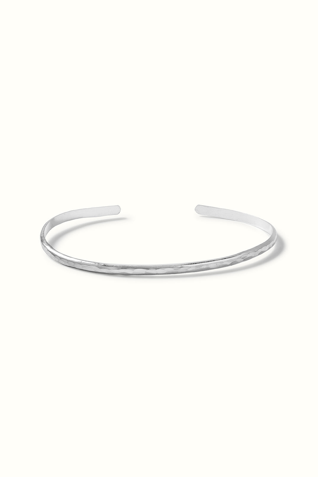 a silver slim cuff bracelet lying on a white surface