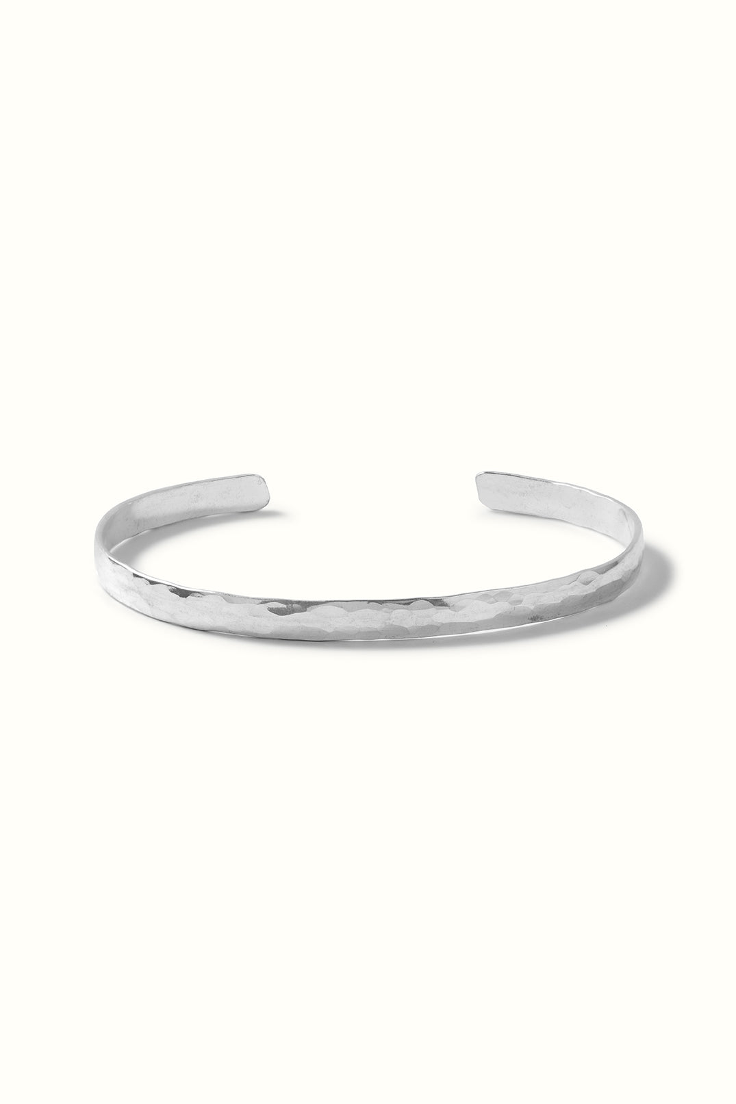a sterling silver hammered cuff bracelet lying on a white surface