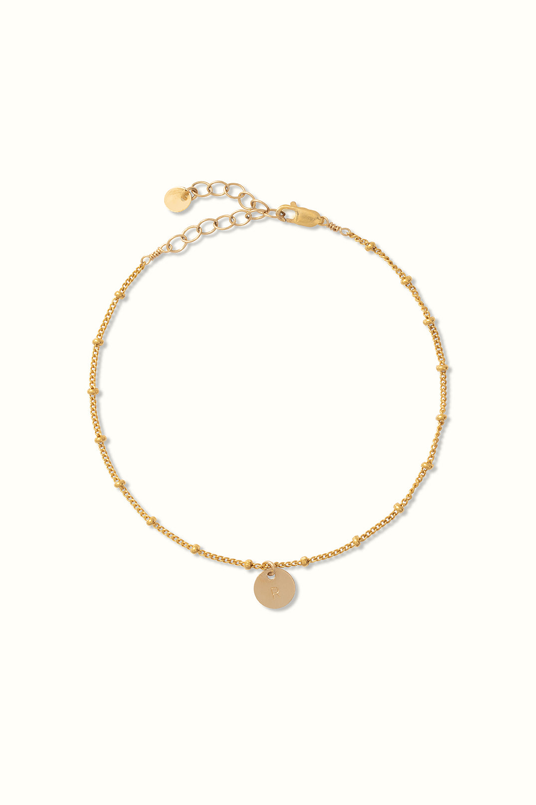 a product close up of a gold filled saturn bracelet with a round initial pendant