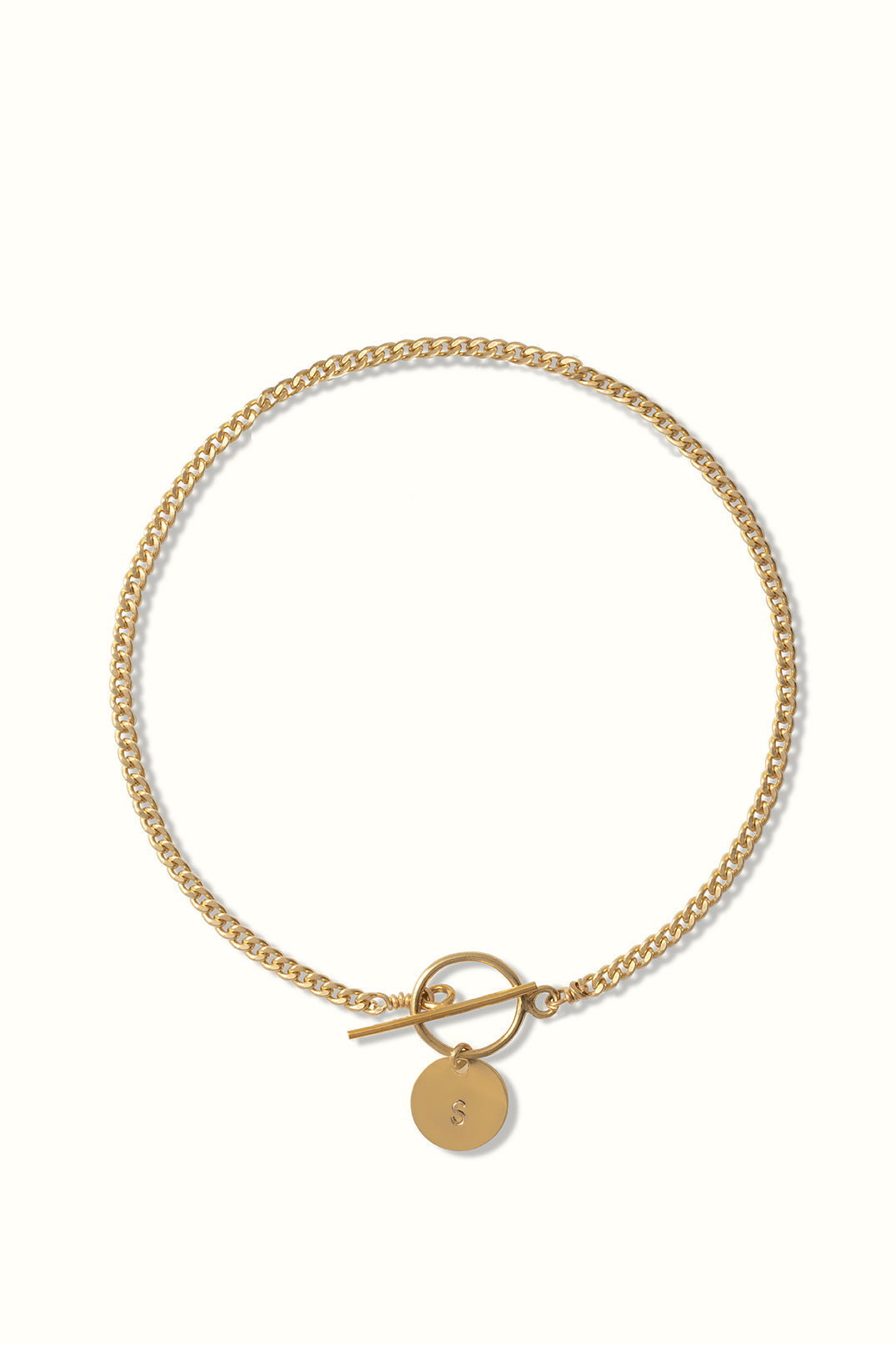 a gold filled curb chain bracelet with a toggle clasp and a round initial pendant