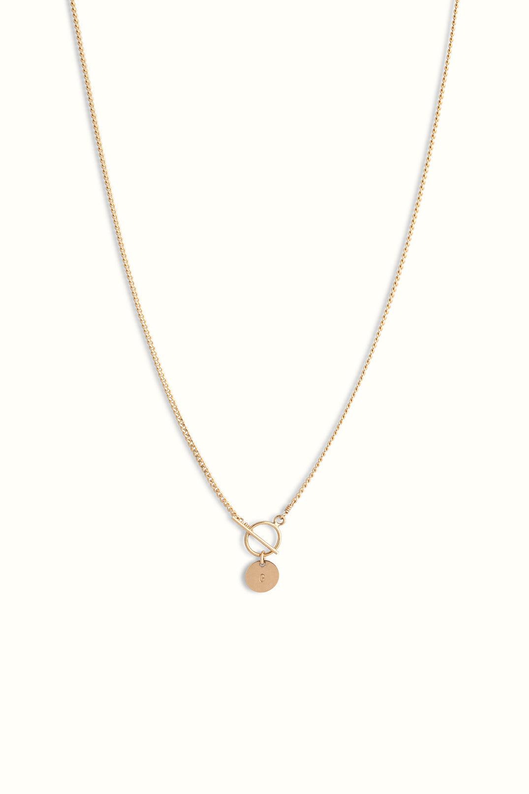 a product close up photo of a gold filled curb chain necklace with a toggle clasp and a round initial pendant