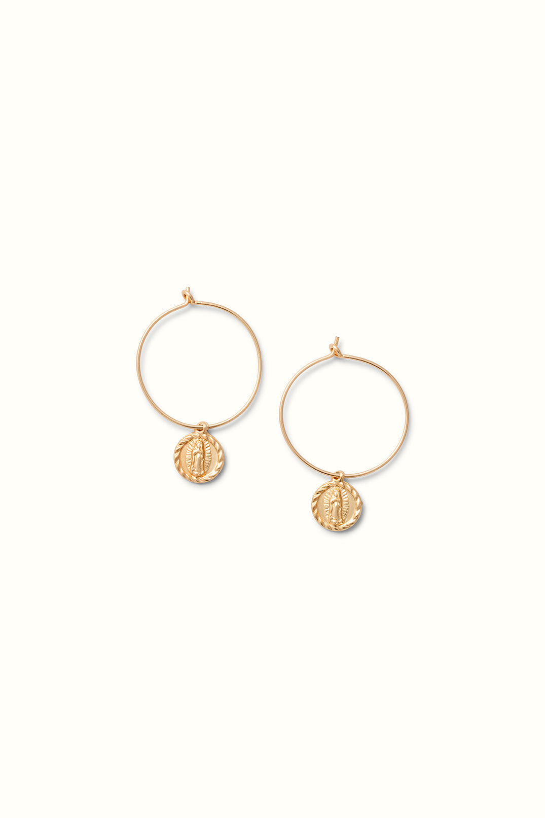 a pair of gold filled wire style earrings with a guadelupe mary round charm lying on a white surface