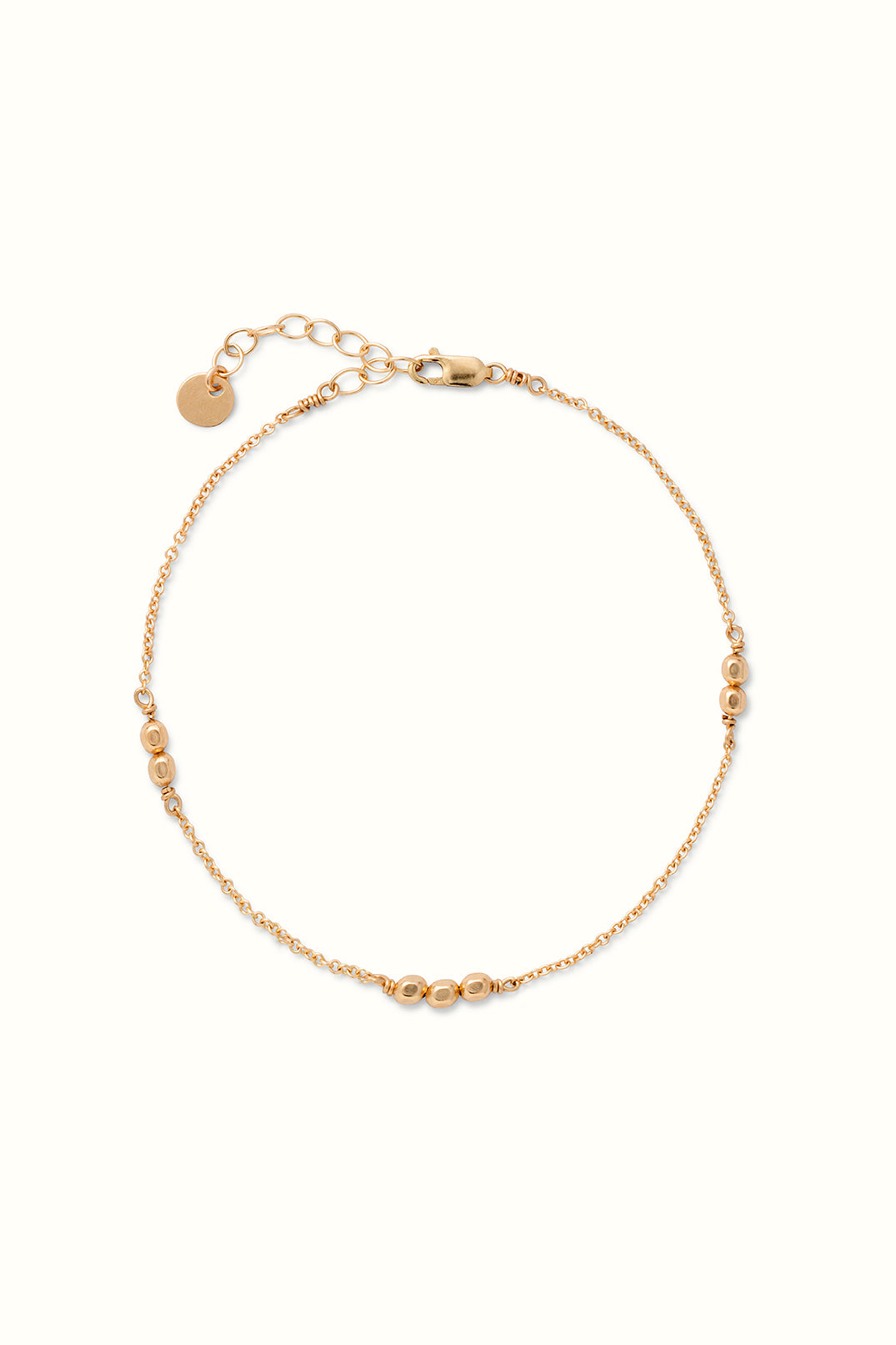 a gold filled beaded chain bracelet lying on a white surface