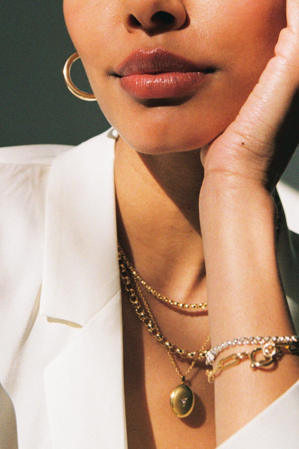 a model wearing a combination of silver and gold filled rolo chain necklaces and bracelets