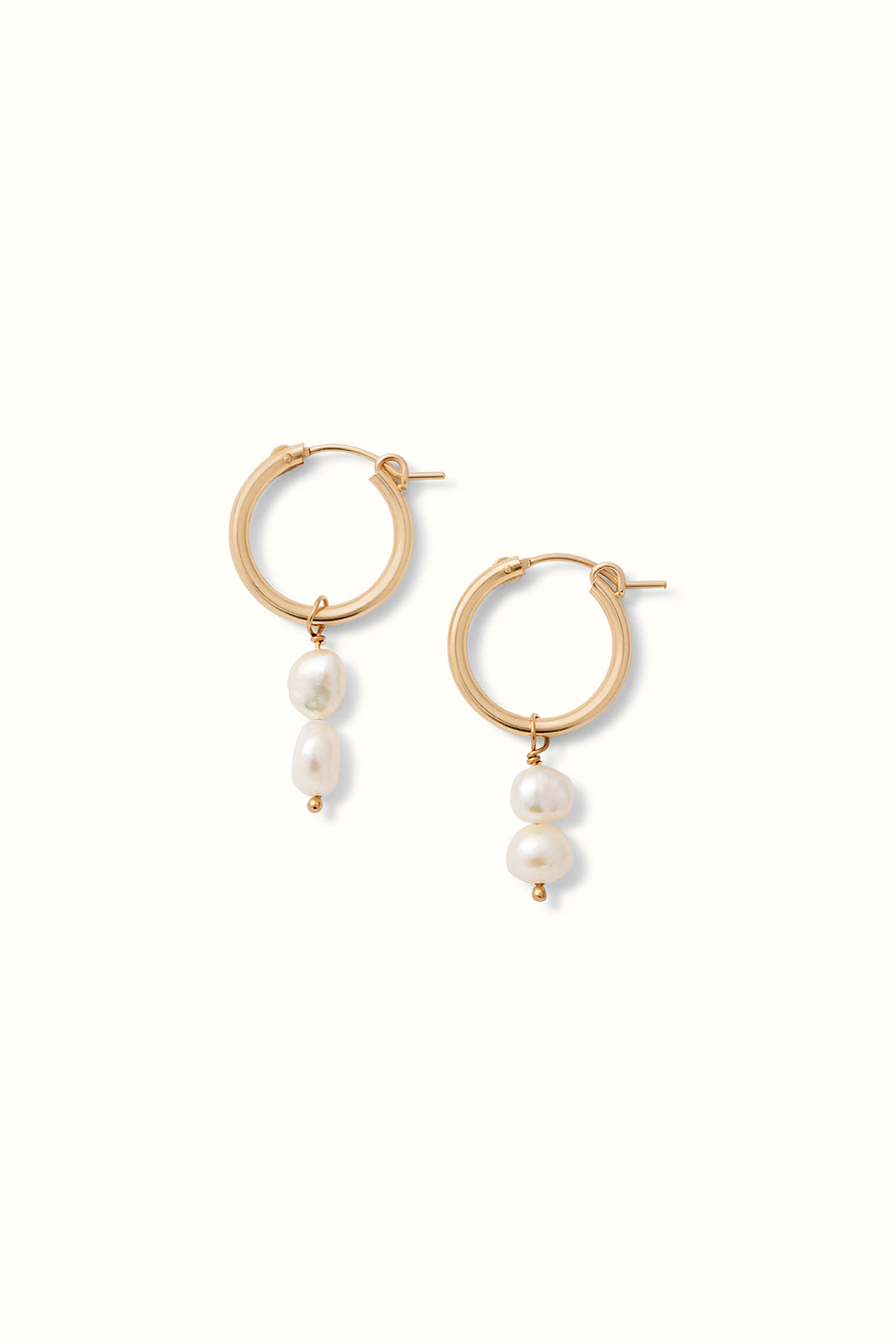 a product shop of a set of gold filled hoops with a pearl drop
