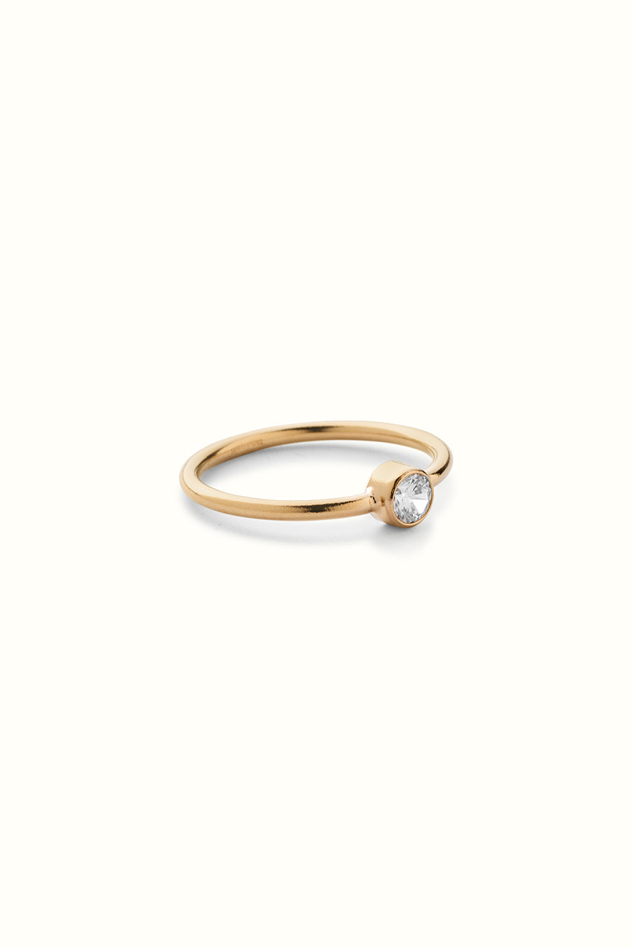 a gold filled finger ring with a set zirconia stone on a white background
