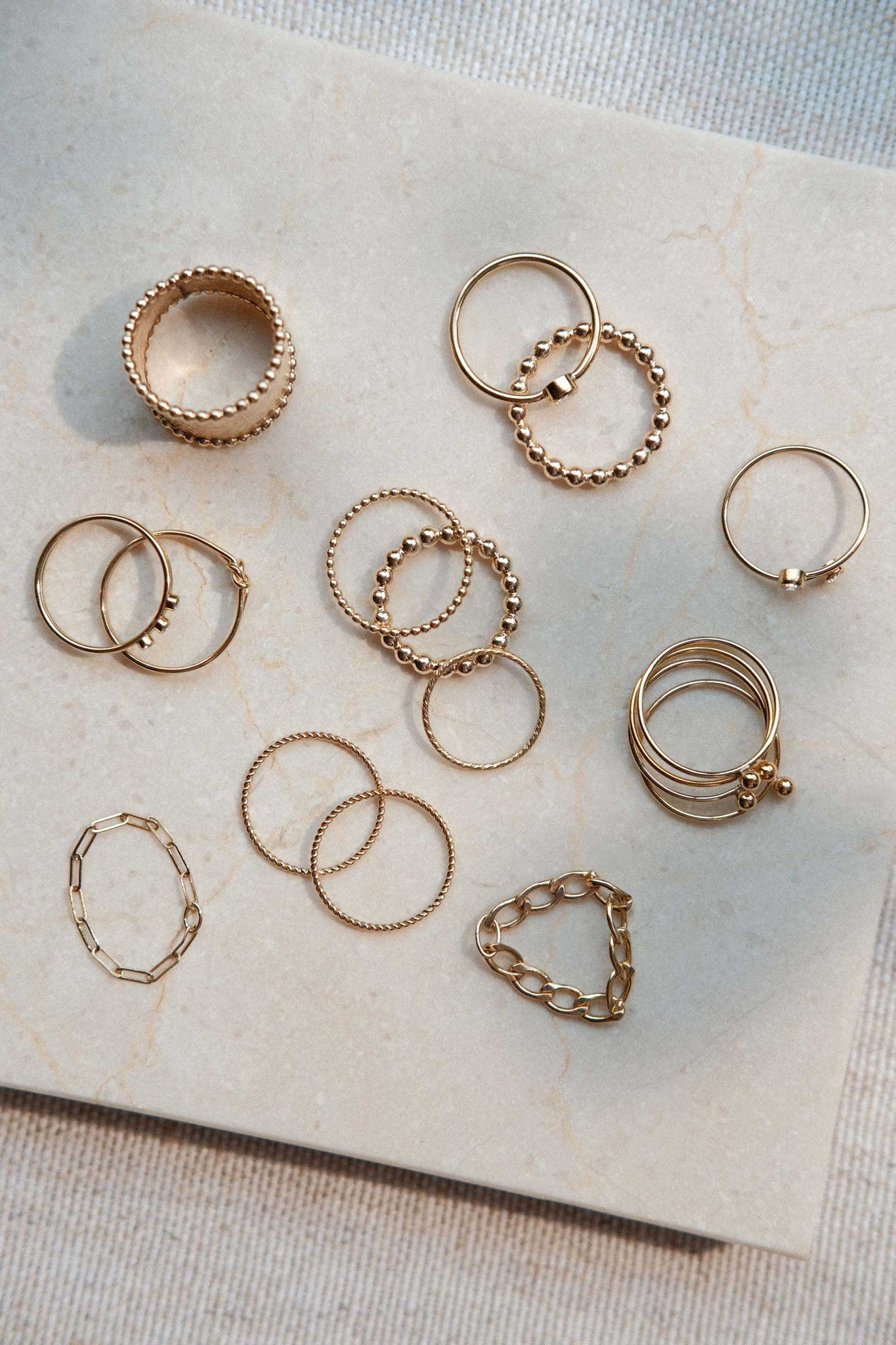 a set of gold filled finger rings on a marble tile surface
