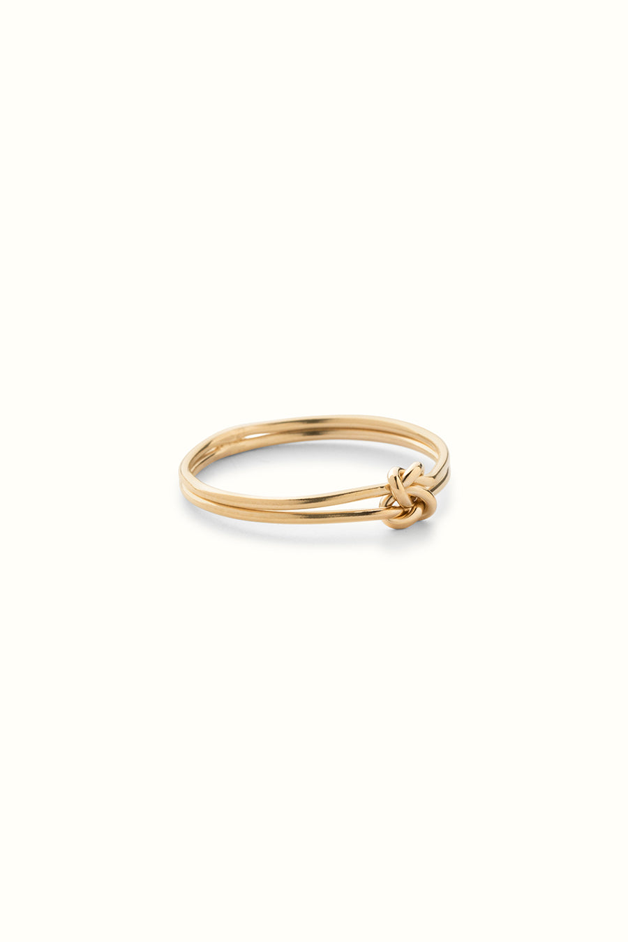 a gold filled love knot wire ring on a white background