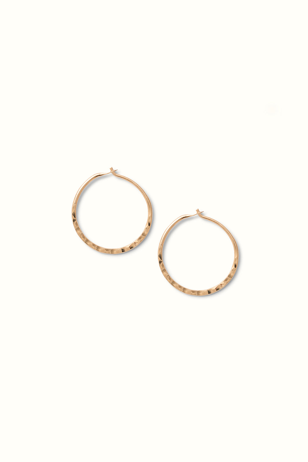 product close up of a pair of hammered gold filled round hoops lying on a white surface