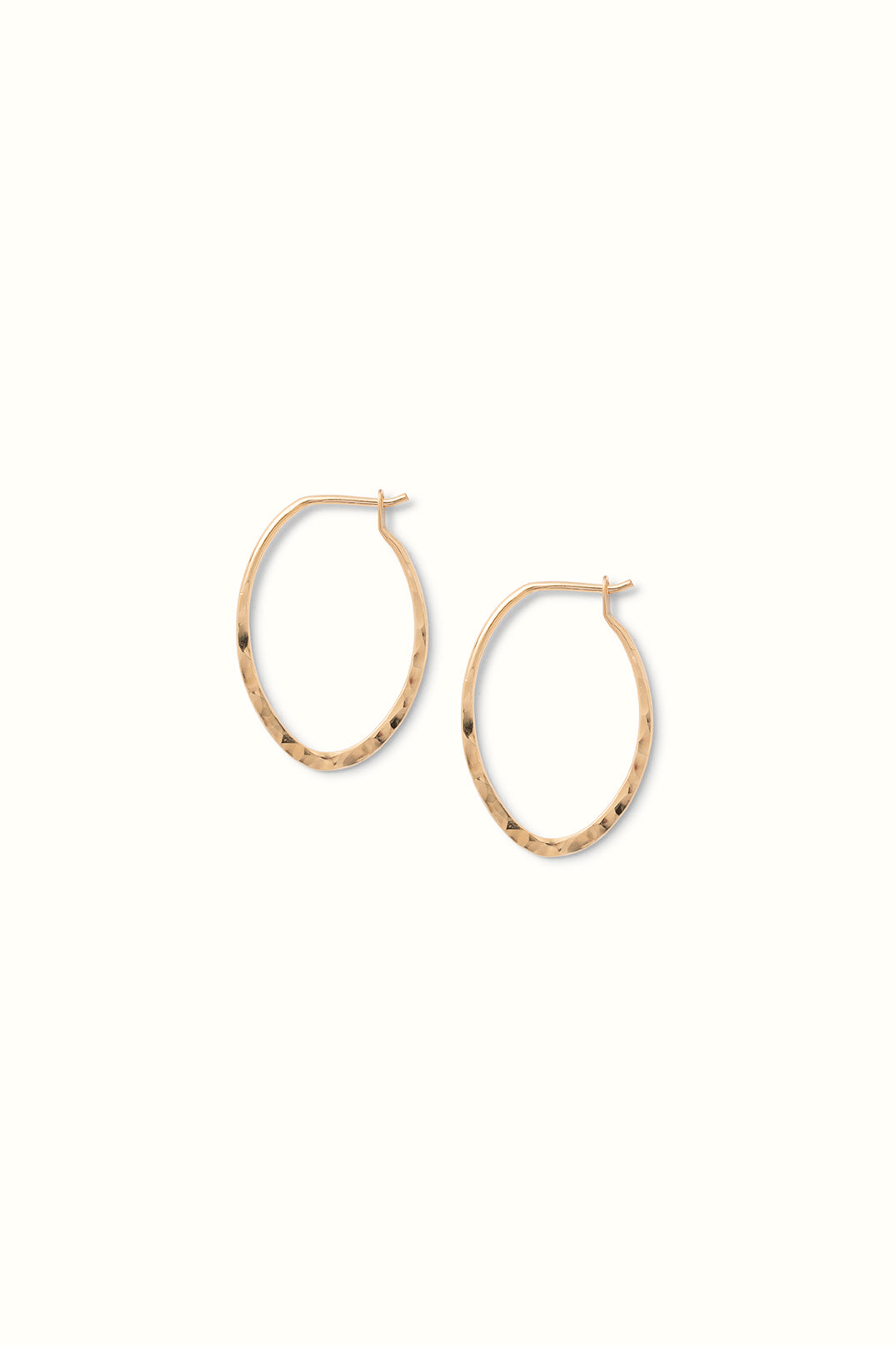 a close up of a pair of gold filled hammered oval hoops lying on a white surface