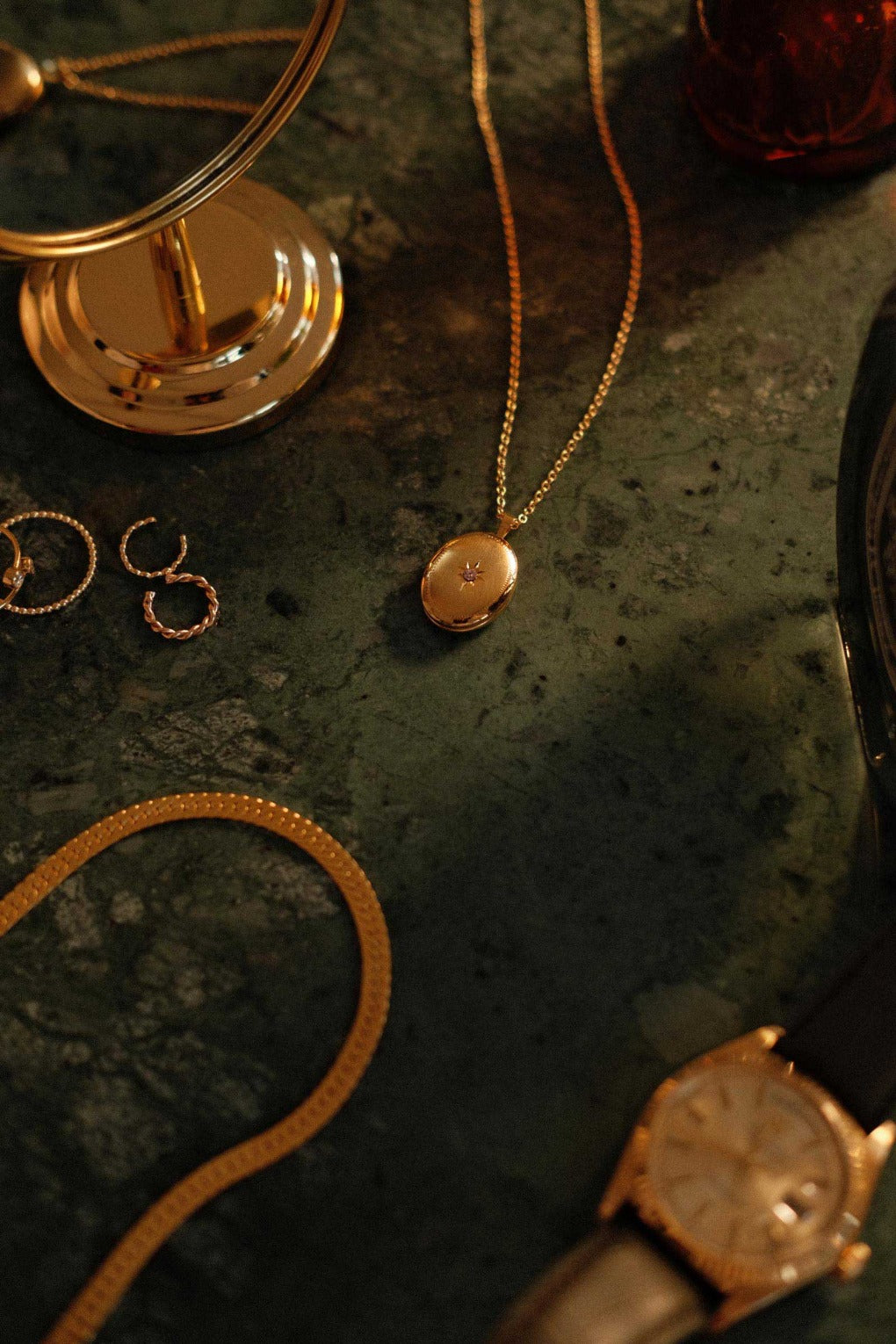 a gold filled locket necklace lying next to other gold filled jewellery on green marble