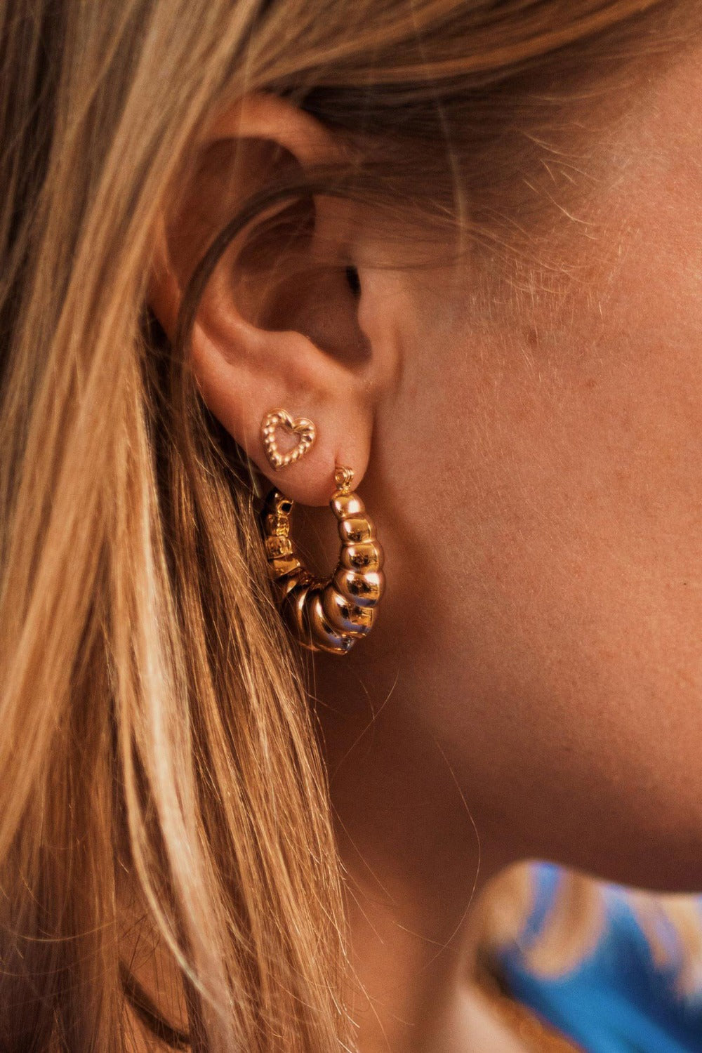 a model wearing a gold filled open heart ribbed stud earring