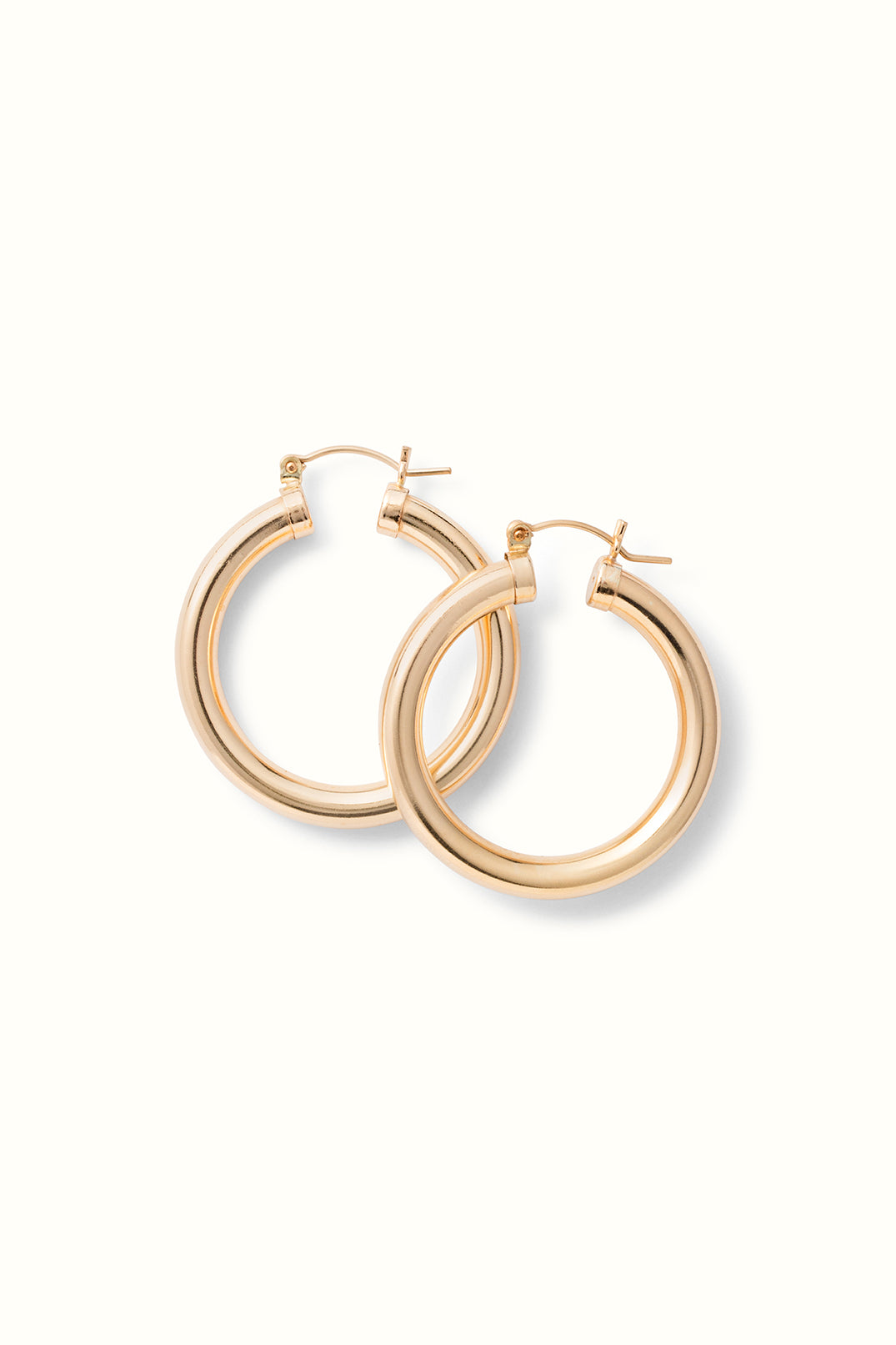 a set of large chunky gold filled hoop earrings lying on a white surface