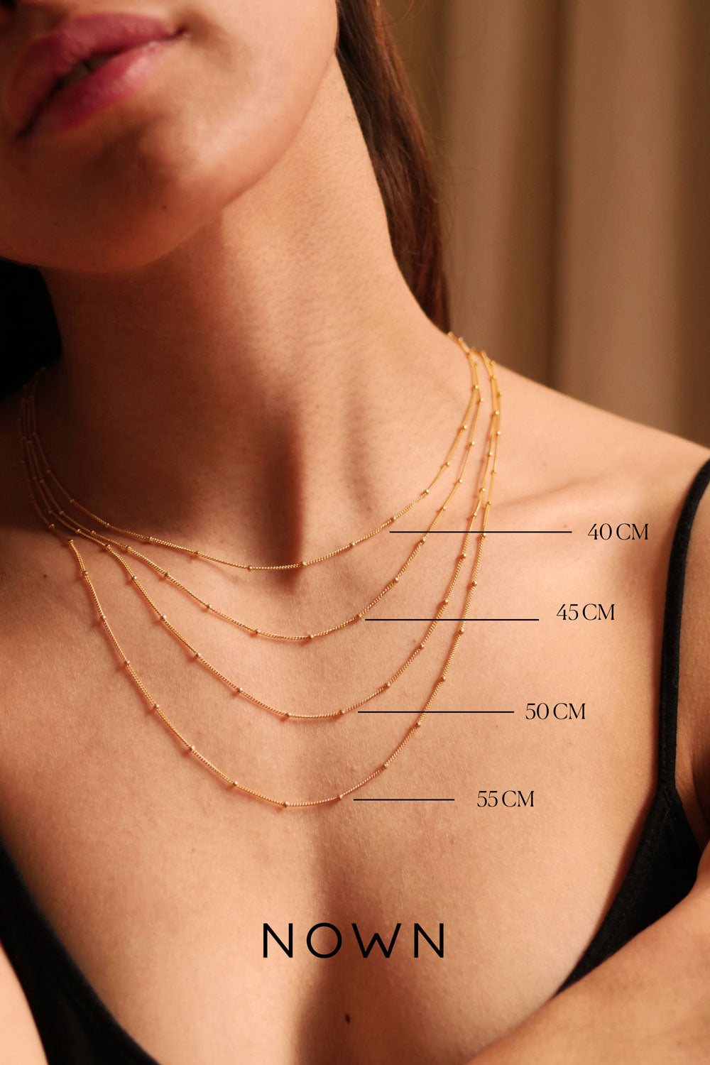 model wearing a collection of sizes of a gold filled necklace