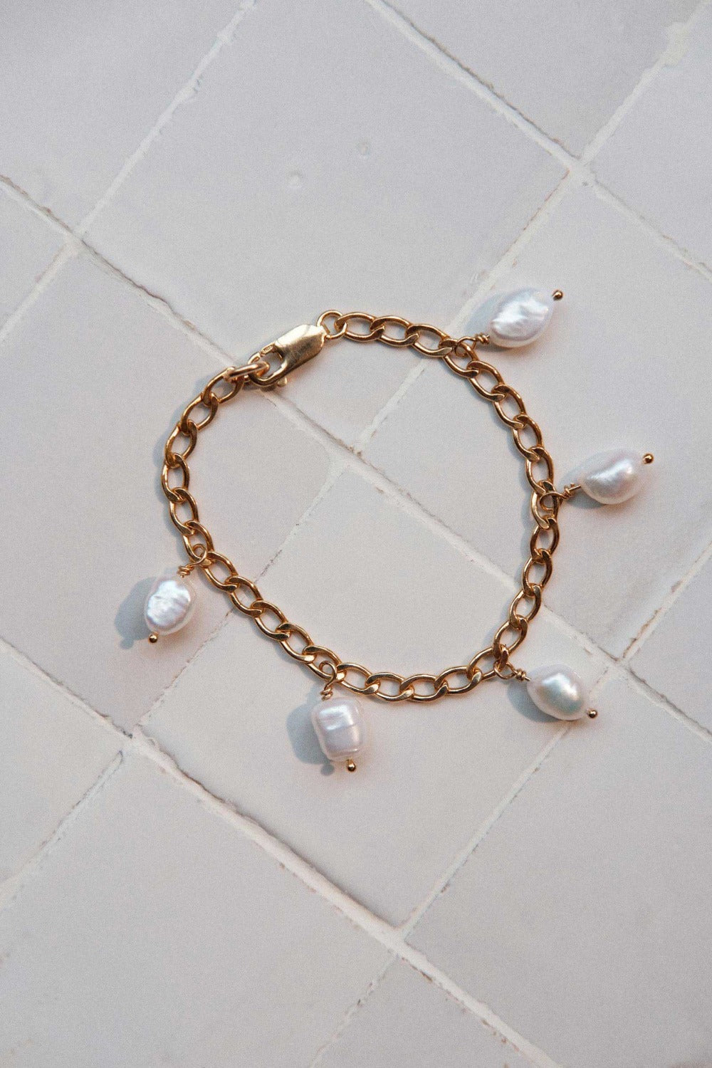 a gold filled curb chain bracelet with pearl drops on a tiled surface